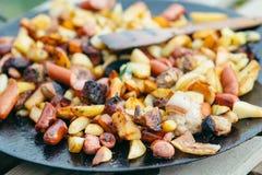 Gebraden aardappels met vlees en worsten die concept het koken op een open brand roosteren Picknick in het weekend Royalty-vrije Stock Foto's