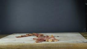 Gebraden baconchef-kok die in zwarte handschoenen ??n enkele plak in zijn handenworpen houden op een houten raad, die zwart bacon stock videobeelden