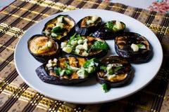 Gebraden blauwe aubergines met vers knoflook en greens op een ronde witte plaat, heet en smakelijk Het eigengemaakte koken royalty-vrije stock afbeeldingen