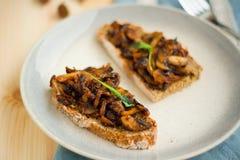 Gebraden champignon met knoflook op geroosterd eigengemaakt brood voor weekendontbijt op gestippelde plaat en met wit kantlint Royalty-vrije Stock Afbeelding