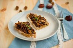Gebraden champignon met knoflook op geroosterd eigengemaakt brood voor weekendontbijt op gestippelde plaat en met wit kantlint Stock Foto's