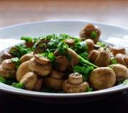 Gebraden champignonpaddestoelen met groene ui Stock Afbeeldingen