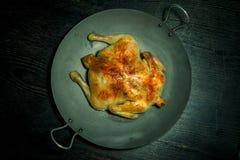 Gebraden chiken op een pan op een zwarte houten lijst gestemd Stock Afbeeldingen