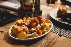 Gebraden die aardappels in kubussen met mayonaise en ketchup worden gesneden stock afbeelding