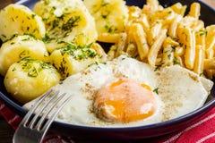 Gebraden die ei met aardappels en gele bonen wordt gediend Stock Foto