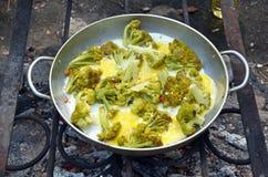 Gebraden die eieren met broccoli, in een grote pan over een kampvuur worden gekookt Stock Afbeeldingen