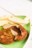 Gebraden die visvleesburgers met frieten op de plaat wordt gediend stock foto's
