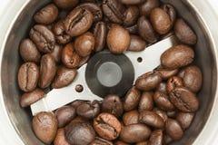 Gebraden donkere koffiebonen in een automatische koffiemolen, de achtergrond van het close-upvoedsel Stock Foto's