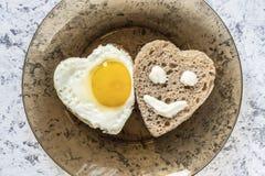 Gebraden ei en brood in de vorm van een hart Smiley op een stuk van brood stock afbeelding