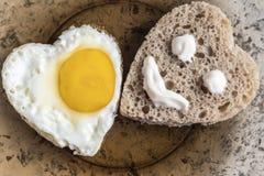Gebraden ei en brood in de vorm van een hart Smiley op een stuk van brood stock foto's