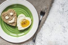 Gebraden ei en brood in de vorm van een hart Smiley op een stuk van brood royalty-vrije stock afbeeldingen
