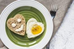 Gebraden ei en brood in de vorm van een hart Smiley op een stuk van brood stock foto