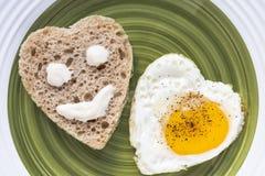 Gebraden ei en brood in de vorm van een hart Smiley op een stuk van brood royalty-vrije stock afbeelding