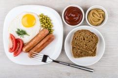 Gebraden ei en worsten in glasplaat, ketchup, mosterd Stock Afbeeldingen