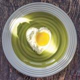 Gebraden ei in hartvorm op een schotel op houten achtergrond royalty-vrije stock fotografie