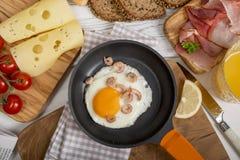 Gebraden ei met garnalen in pan, kaas, ham, brood en broodjes Royalty-vrije Stock Afbeeldingen