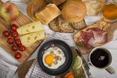 Gebraden ei met garnalen in pan, kaas, ham, brood en broodjes, koffie Royalty-vrije Stock Foto's