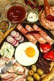 Gebraden ei op een houten raad Een hartelijk ontbijt met ham en groenten Eieren en ham stock afbeeldingen
