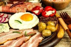 Gebraden ei op een houten raad Een hartelijk ontbijt met ham en groenten Eieren en ham stock afbeelding