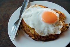 Gebraden ei op ronde witte plaat op houten lijst Gebraden eieren voor ontbijt Stock Afbeeldingen