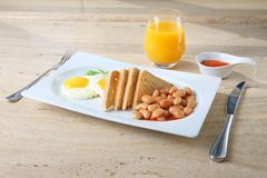 Gebraden eieren, bonen en toost op een plaat met jam, honing en sap Stock Foto