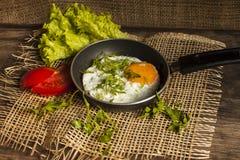 Gebraden eieren in een kleine pan op een raad Stock Foto's