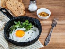 Gebraden eieren in een pan, brood, zout, vork op houten achtergrond stock foto's