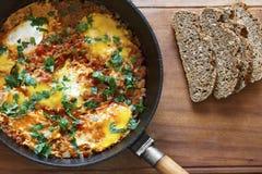 Gebraden eieren in een pan met graangewassenbrood Shakshukamening van hierboven stock afbeeldingen