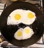 Gebraden eieren in een pan met kersentomaten en brood voor ontbijt op een zwarte achtergrond stock afbeeldingen