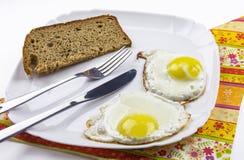 Gebraden eieren en zwart brood op een witte plaat Royalty-vrije Stock Foto