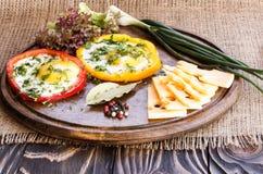 Gebraden eieren in kleurrijke peper op een bruine oude houten raad Stock Foto's