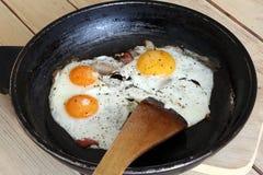Gebraden eieren met bacon op de pan - hartelijk ontbijt Stock Afbeelding