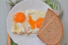 Gebraden eieren met brood op een plaat Stock Foto