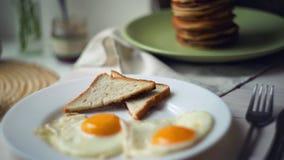Gebraden eieren met broodtoosts en pannekoekstapel Gekookte eieren, geroosterde broodplak stock videobeelden