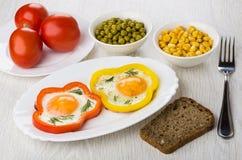 Gebraden eieren met paprika's, brood, groene erwten, graan, tomaten stock afbeelding