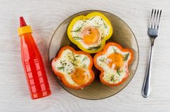 Gebraden eieren met paprika's, ketchup en vork op lijst stock foto