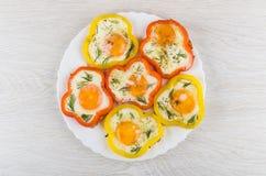 Gebraden eieren met rode en gele paprika's in schotel royalty-vrije stock foto's