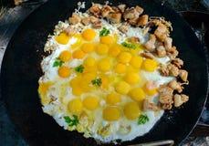 Gebraden eieren met stukken die van varkensvlees op een grote vlakke pan, in openlucht koken royalty-vrije stock afbeelding