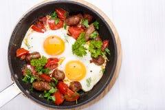 Gebraden eieren met worsten en groenten in een pan stock afbeelding