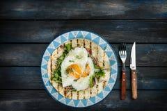 Gebraden eieren op bloemtortilla met groene salade en kaas Nuttig ontbijt of lunchidee Vorkmes en mooie schotel royalty-vrije stock afbeeldingen