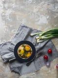 Gebraden eieren op de plaat met kersentomaten, kruiden en groene uien in rustieke stijl, hoogste mening, ruimte voor tekst Royalty-vrije Stock Fotografie