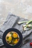 Gebraden eieren op de plaat met kersentomaten, kruiden en groene uien in rustieke stijl, hoogste mening, ruimte voor tekst Voedza Stock Fotografie