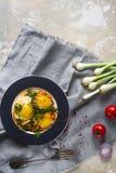 Gebraden eieren op de plaat met kersentomaten, kruiden en groene uien in rustieke stijl, hoogste mening Voedzaam organisch ontbij Stock Afbeelding