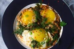 Gebraden eieren op de plaat met kersentomaten, kruiden en groene uien in rustieke stijl, hoogste mening Voedzaam organisch ontbij Stock Fotografie