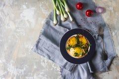 Gebraden eieren op de plaat met kersentomaten, kruiden en groene uien in rustieke stijl, hoogste mening Voedzaam organisch ontbij Royalty-vrije Stock Fotografie