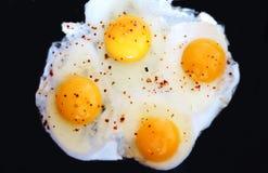 Gebraden eieren op een zwarte achtergrond Stock Afbeeldingen