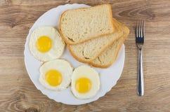 Gebraden eieren, stukken van brood in witte schotel en vork stock foto