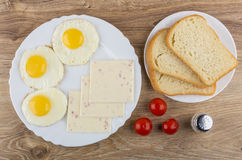 Gebraden eieren, stukken van kaas in schotel, brood, tomaten royalty-vrije stock fotografie