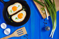 Gebraden eieren in toost met kruiden en de lenteui op blauwe houten Royalty-vrije Stock Afbeeldingen