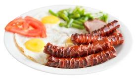 Gebraden eieren, worsten, tomaat op geïsoleerde plaat Stock Afbeelding